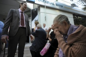 A bank manager explains the situation to pensioners waiting outside a branch of the National Bank of Greece hoping to get their pensions, in Thessaloniki, Greece June 29, 2015. Greece closed its banks and imposed capital controls on Sunday to check the growing strains on its crippled financial system, bringing the prospect of being forced out of the euro into plain sight.  REUTERS/Alexandros Avramidis